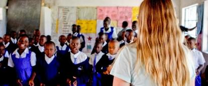 Students stand and listen to the Projects Abroad volunteer teaching them in Kenya